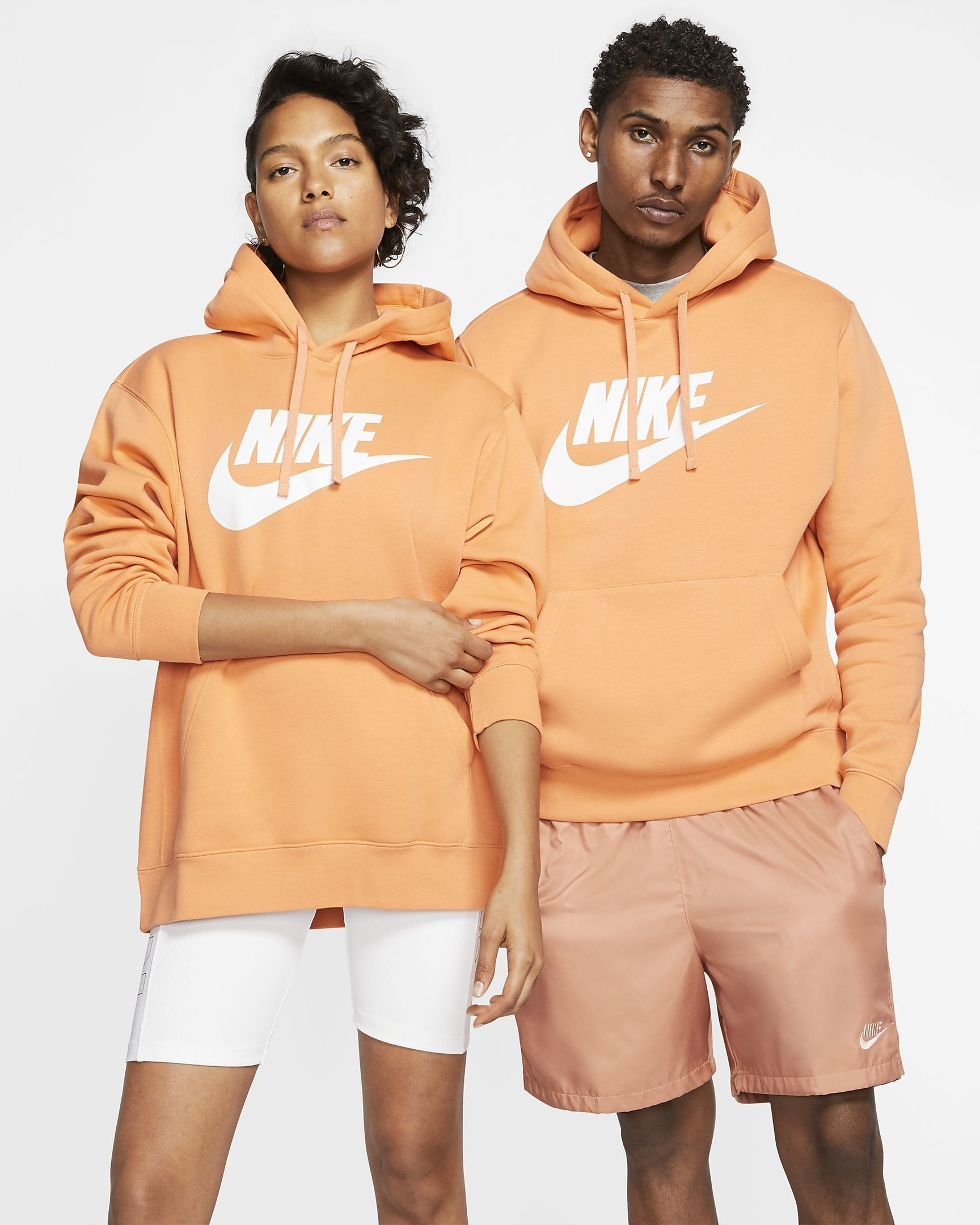 two models wearing the pullover hoodie in light orange with the Nike logo in white on the front of the hoodie