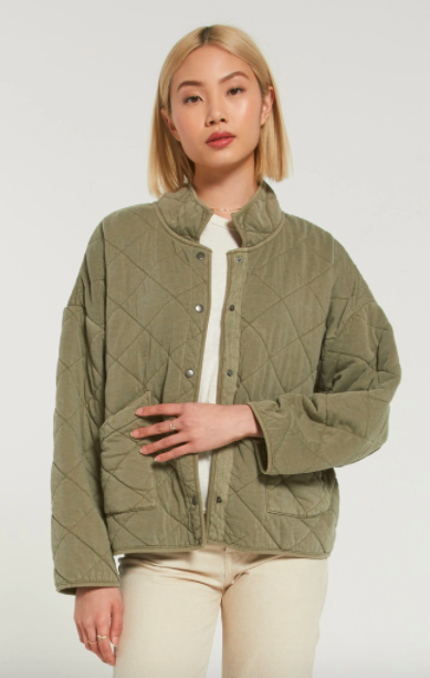 model wearing olive green light puffer jacket in quilted pattern