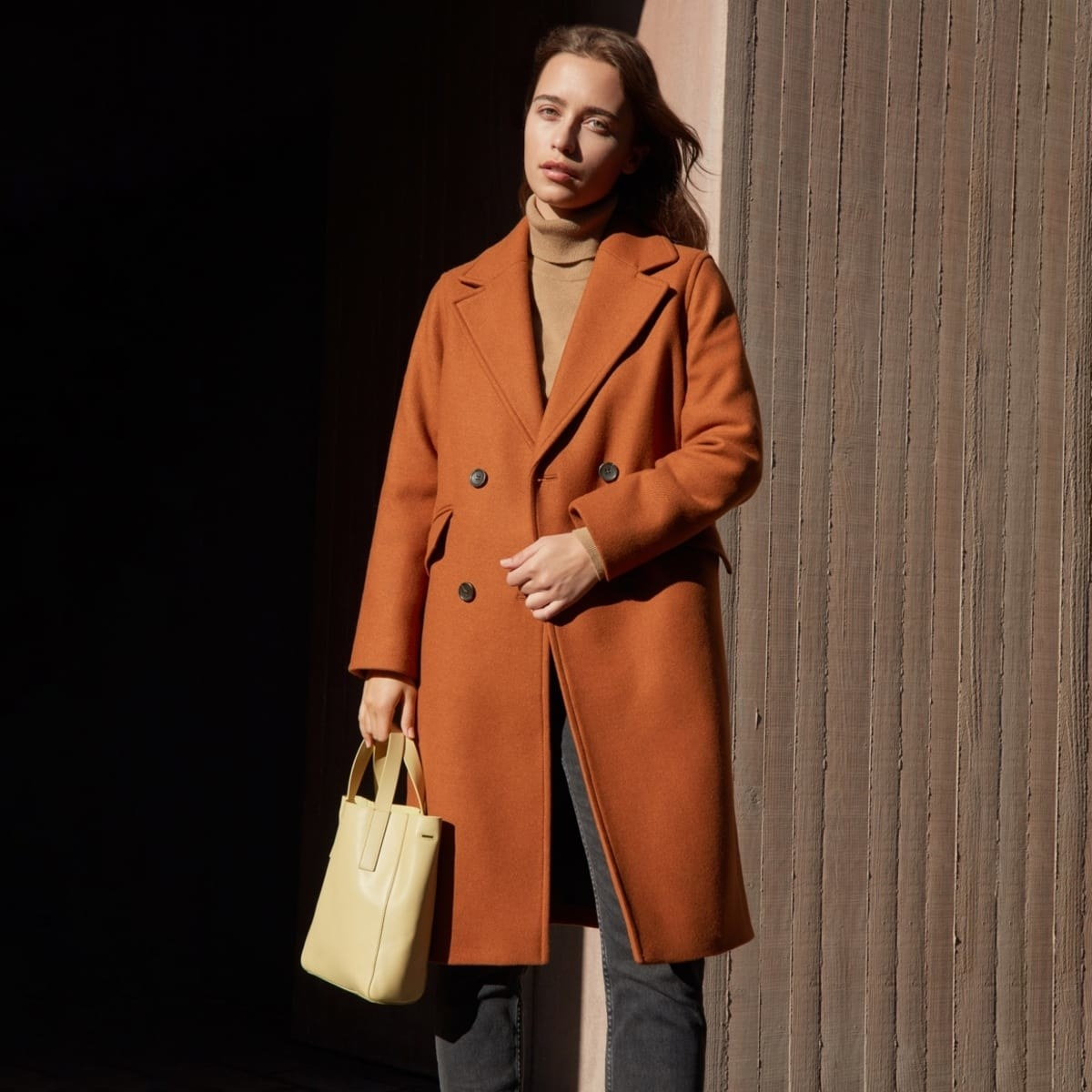 Model wearing the double-breasted coat in the color toffee