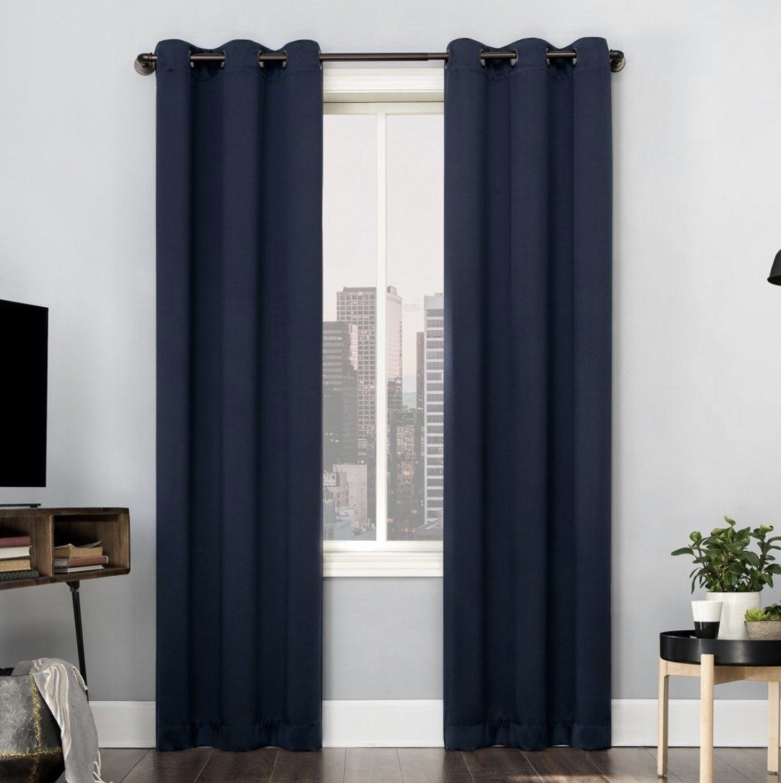 A pair of navy blue blackout curtain panels hung in front of a window in a living room