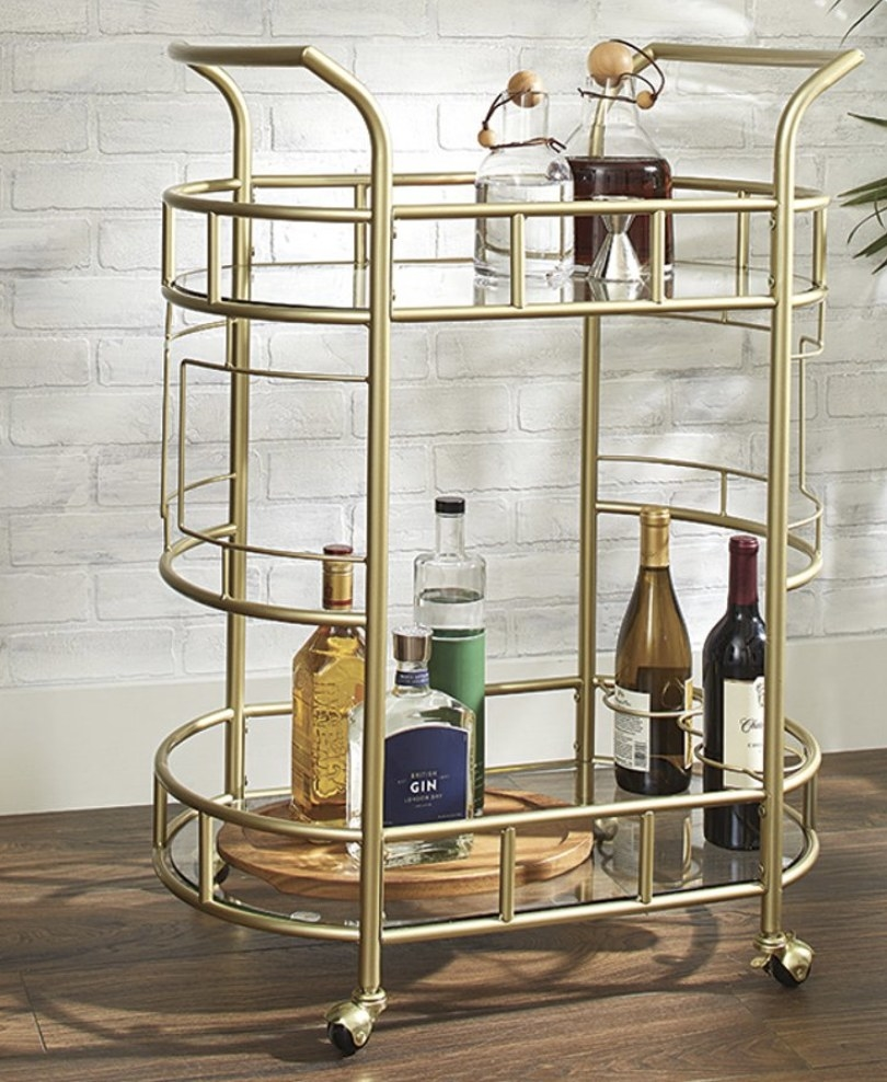A gold chrome bar cart with wheels with two tiers and bottles of liquor placed on them