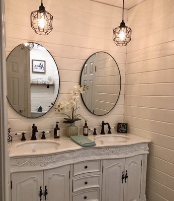 Reviewer image of two of the caged pendant lights hung above two bathroom sinks