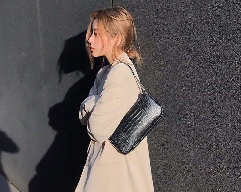 Model wearing the black faux leather purse