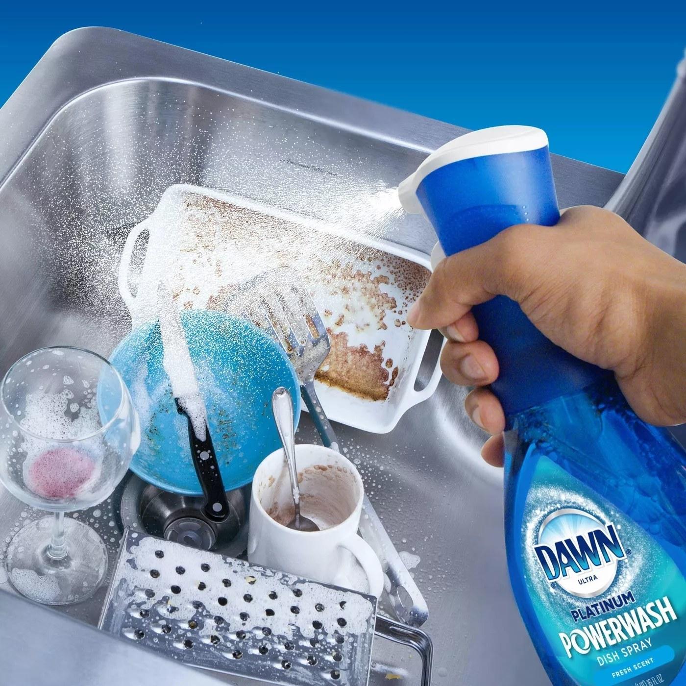 A model spraying Dawn's Platinum Powerwash Dish Spray on a sink full of dirty dishes
