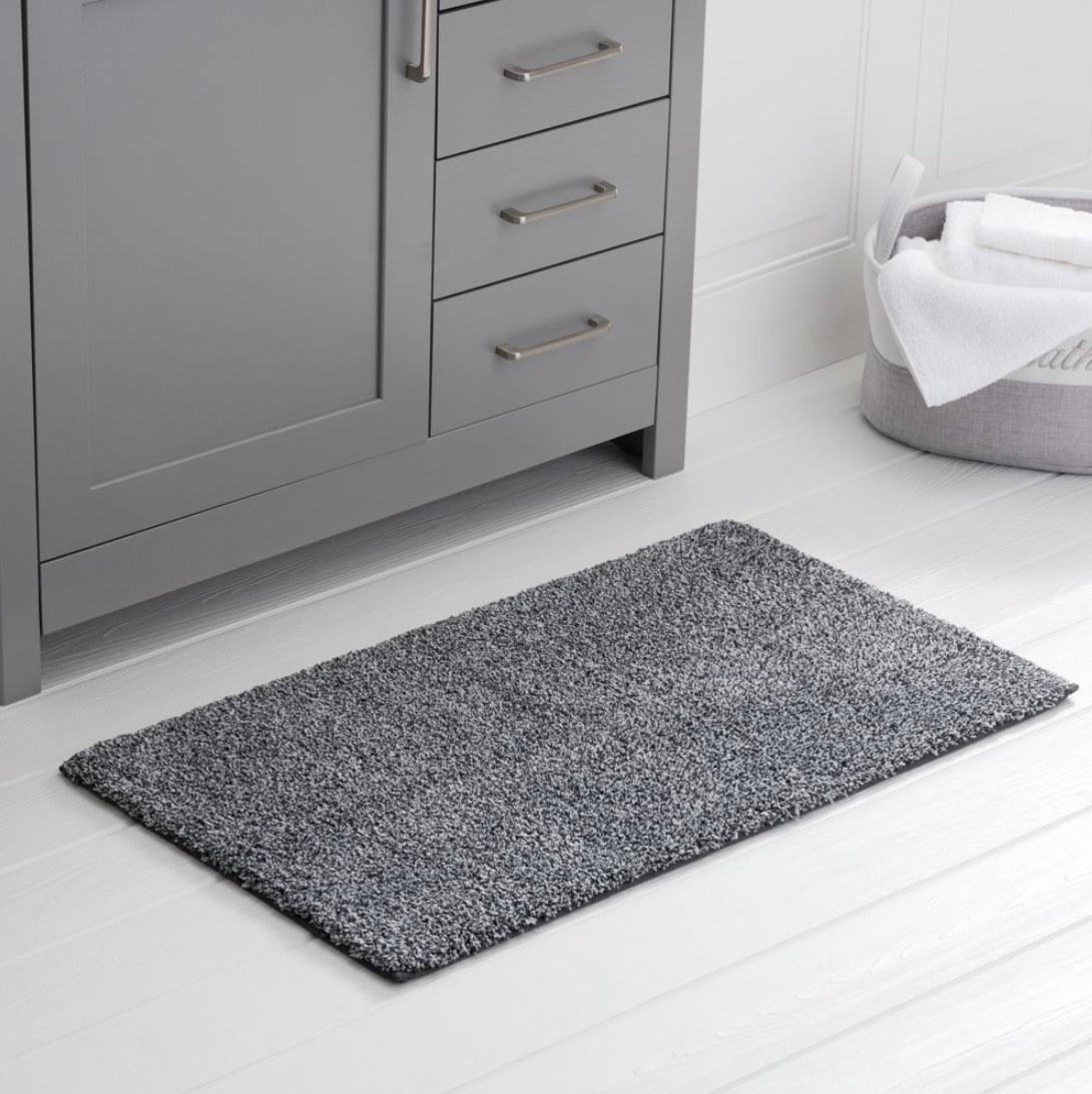 A plush dark grey bath mat in front of a bathroom sink