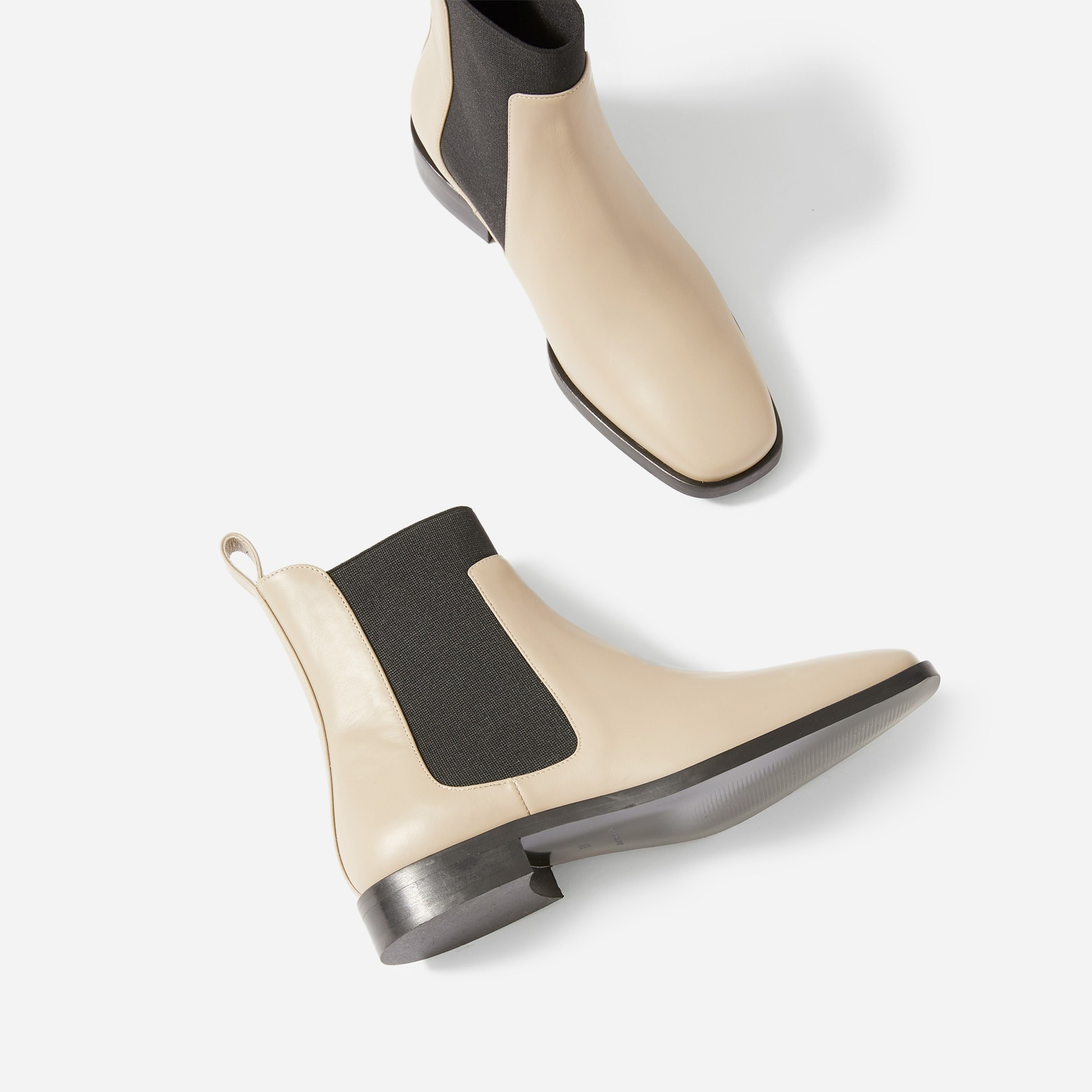 the chelsea boots in an off white color with a strechy black side panel