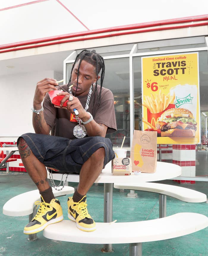 Travis Scott eats fries outside a McDonald's, promoting the new Travis Scott Meal
