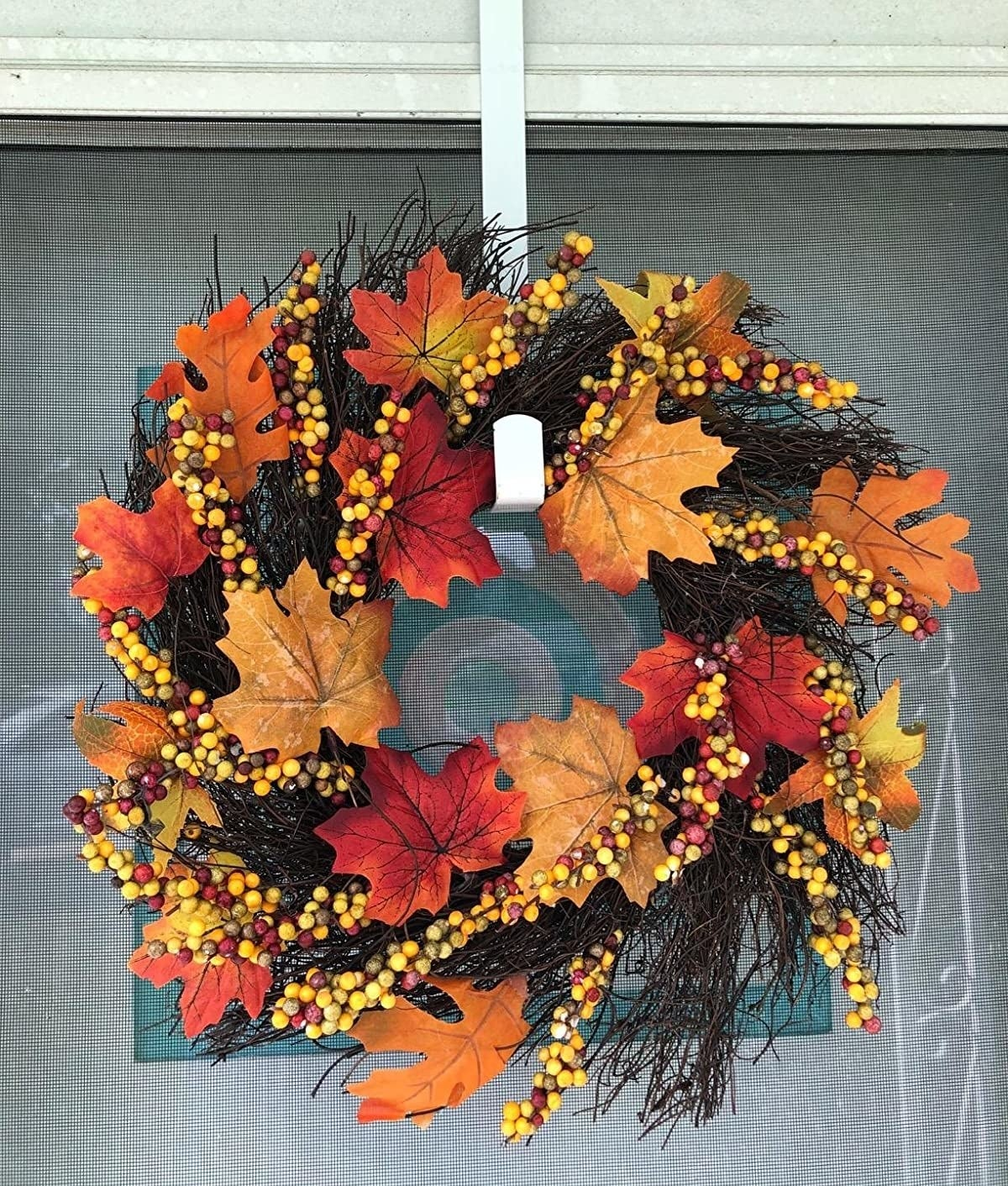 The wreath is full of colorful artificial maple leaves and berries and brown sticks