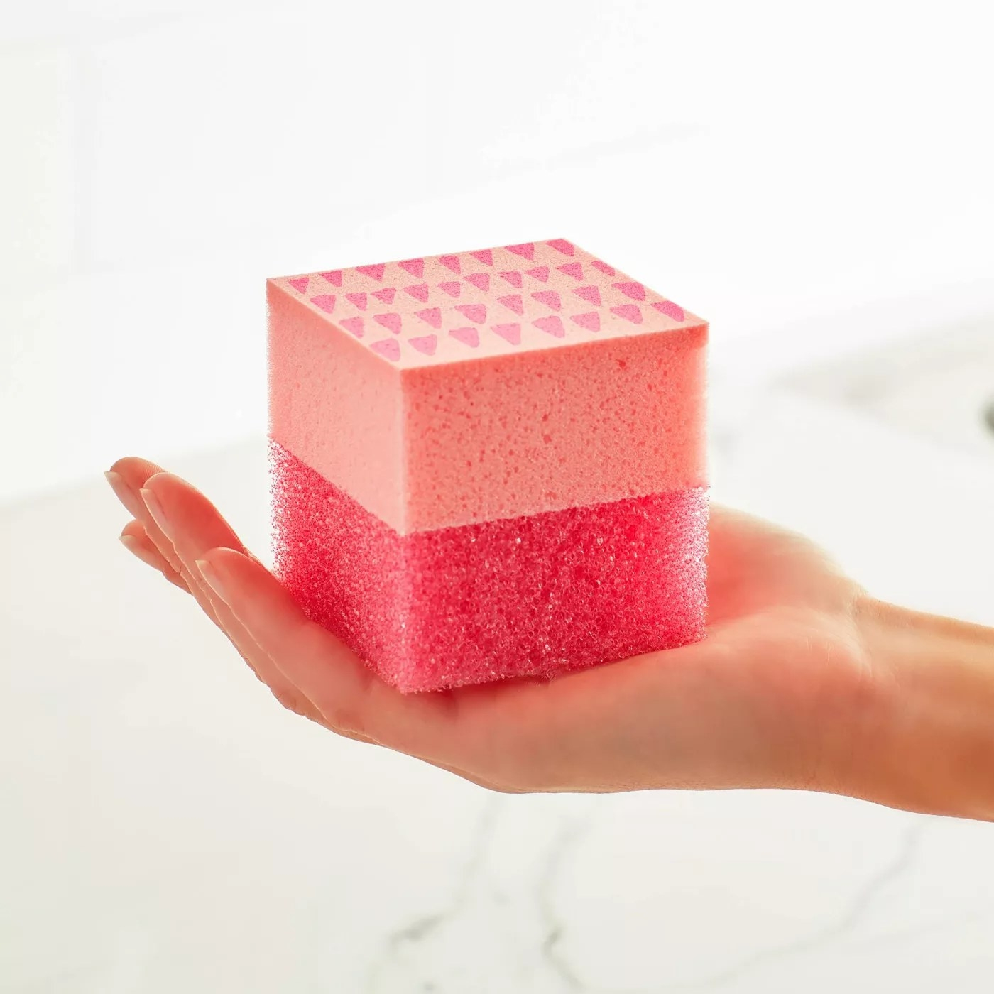 A model holding a pink, cube-shaped sponge with a soft side and a scrubby side