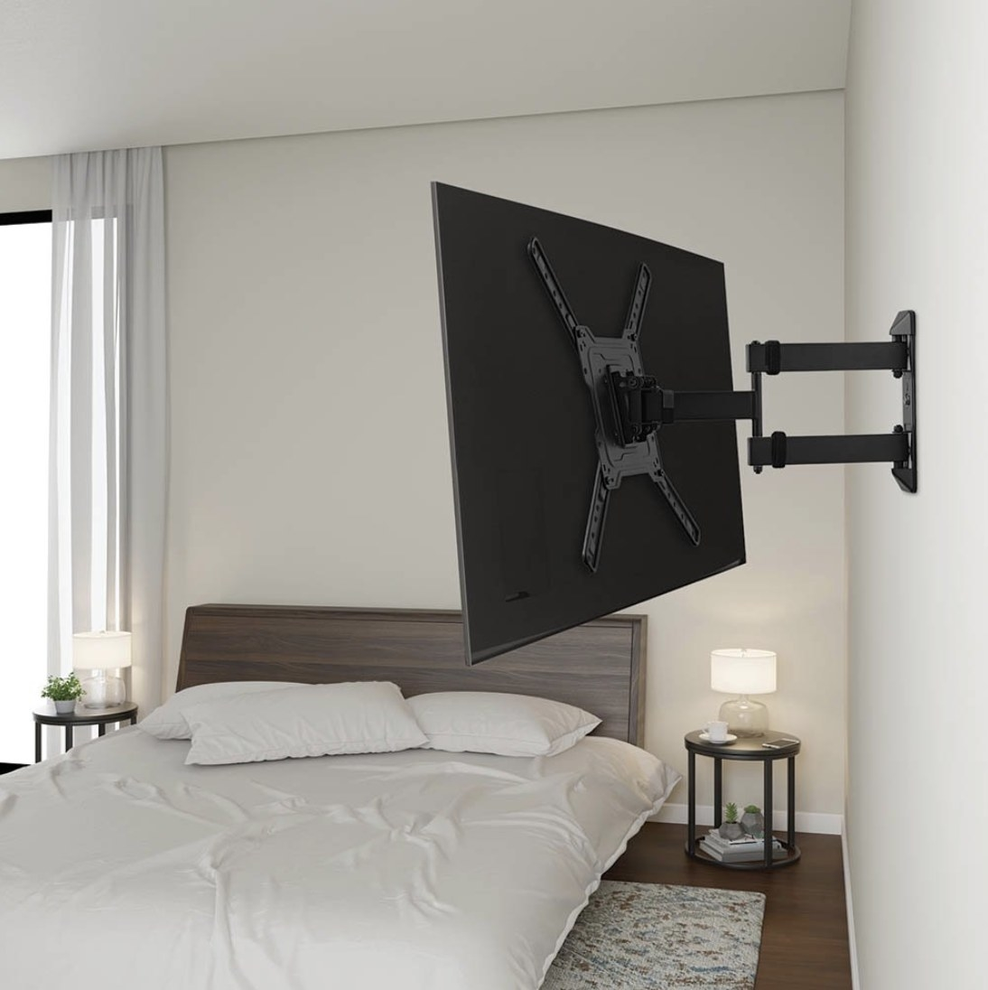 A TV mounted on the wall with a swivel mount in a bedroom