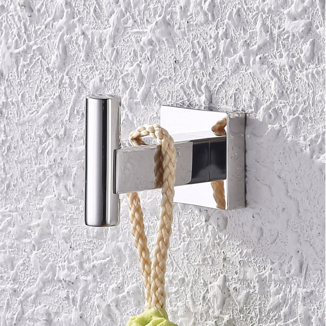 A chrome wall hook installed to a wall holding with a loofah hanging off of it