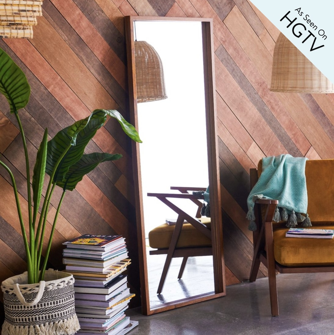 A floor mirror with a wooden frame leaning against a wall in a living space next to a chair and books