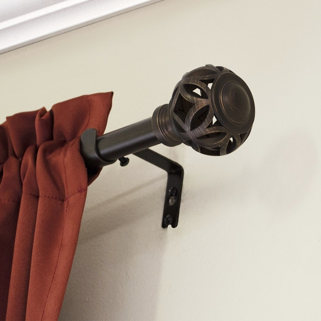 A corner of a mounted curtain rod showcasing the brushed nickel and detail on the end ball
