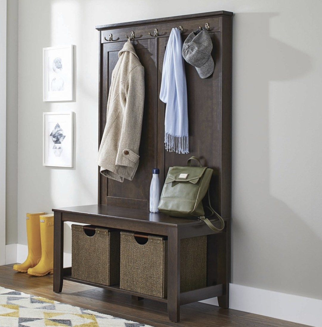 A hall tree bench in an entryway with baskets on the bottom shelf and accessories hanging on the hooks
