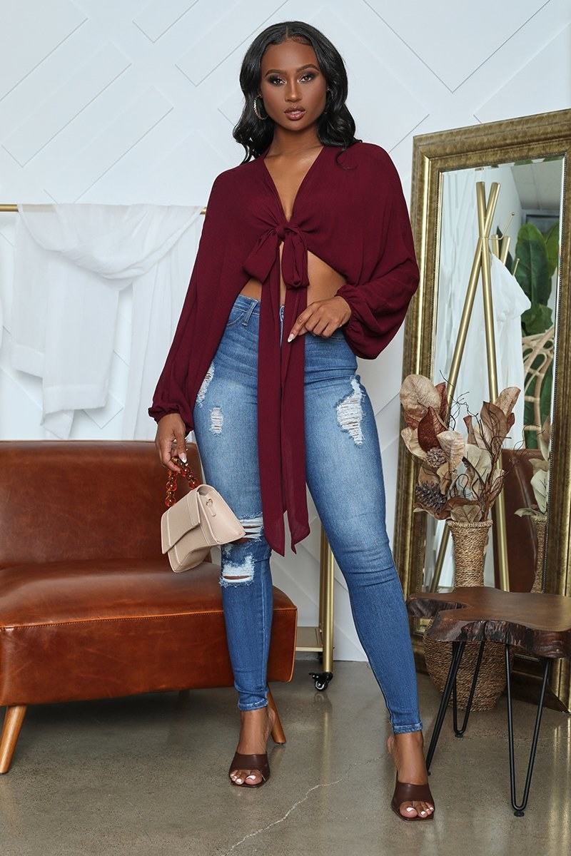 A model wearing the very cropped long-sleeved burgundy top with a plunging neckline and a tie at the bust with high-waisted jeans