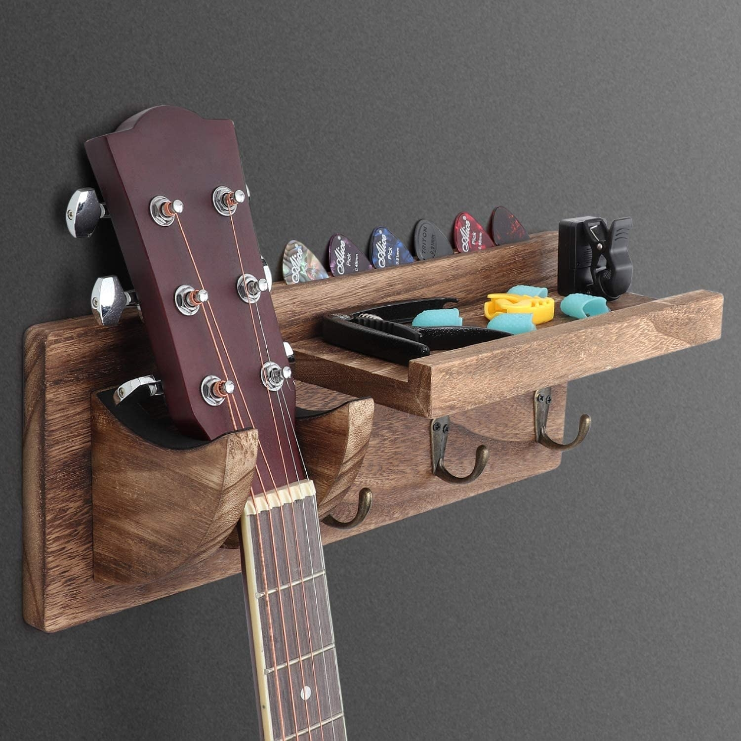 The guitar hanger holding a guitar, a capo, some fingerpicks, a clip on tuner, and some guitar picks