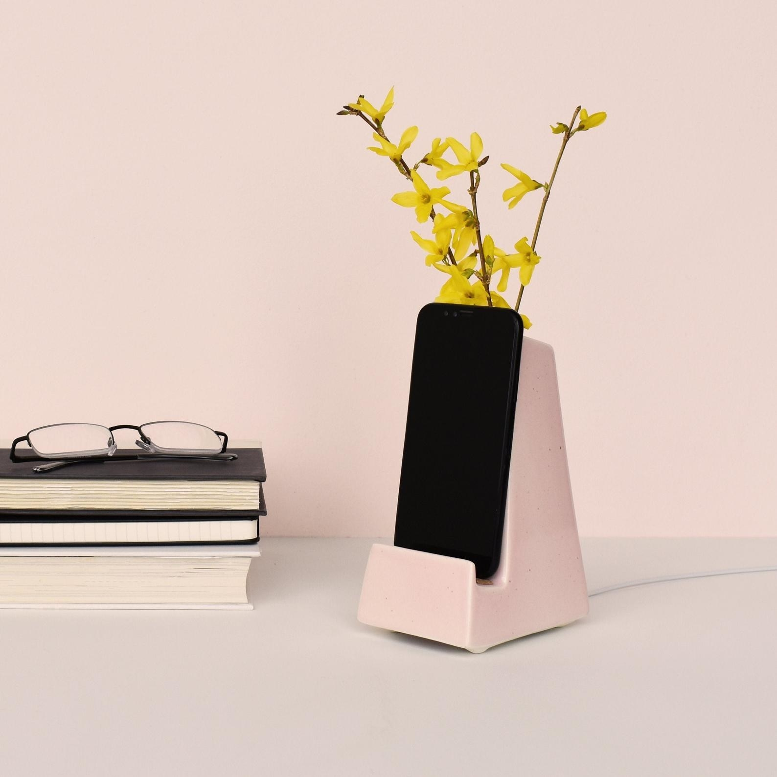 a pink phone dock with a yellow flower sticking from the vase portion on the back and a black cell phone sitting on the front