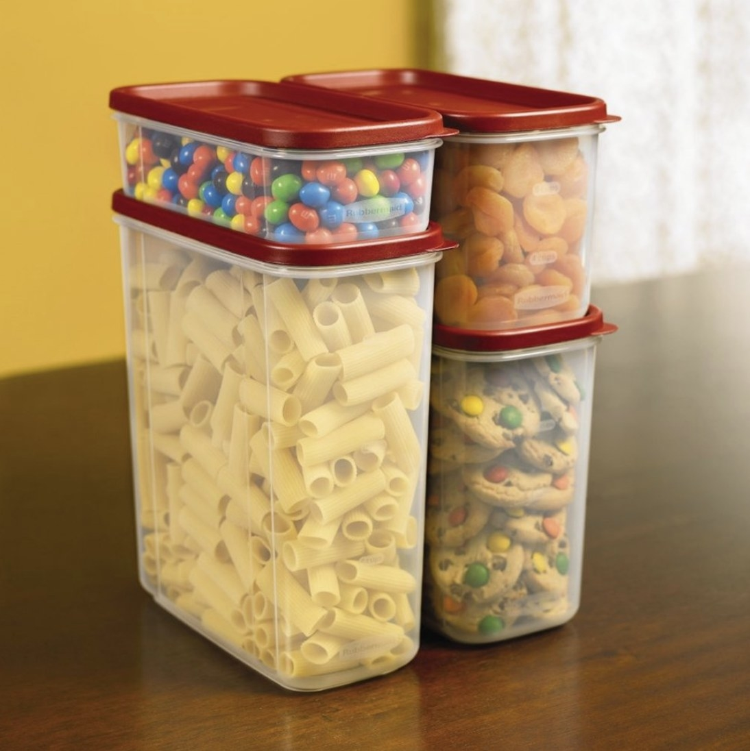 Four clear containers of varying sizes stacked with food inside