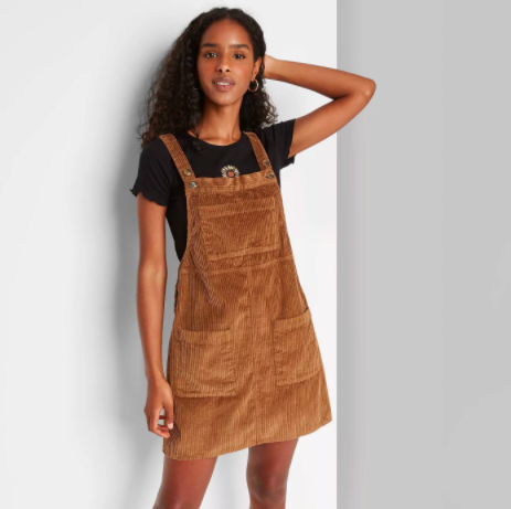 model wearing a brown corduroy pinafore dress over a black T-shirt