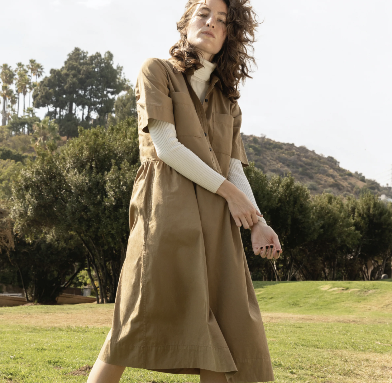 A model in a khaki short-sleeved button down dress with front pockets on the chest