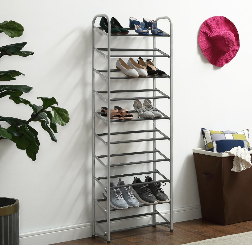 The metal shoe rack holding tennis shoes and sandals
