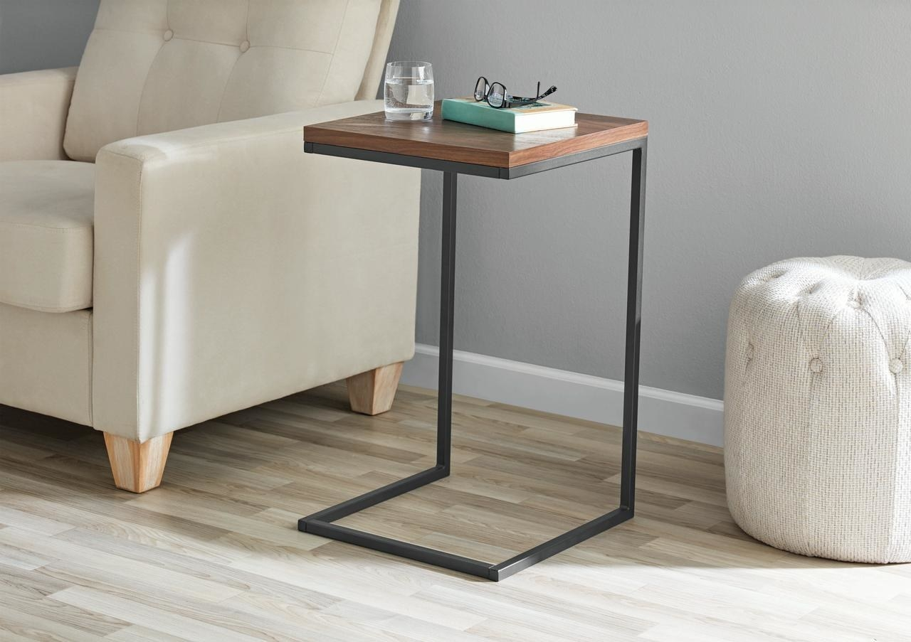 A black c table with a dark wood finish on the surface