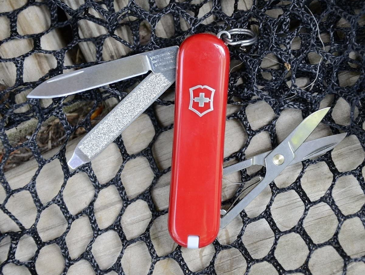 A red Swiss Army knife with scissors, a blade, and a file