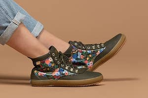 a model in green rubberized boots with rifle paper floral accents