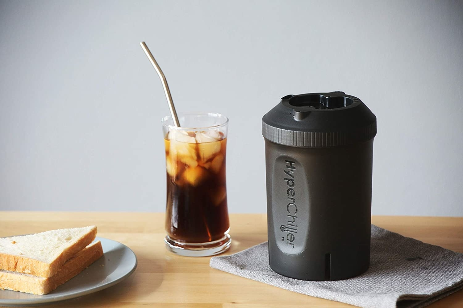 The beverage chiller next to a glass of iced coffee on a butcher block counter