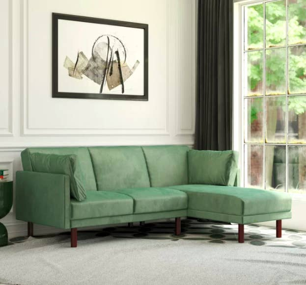 Velvet green sectional couch against a white wall with a painting above it