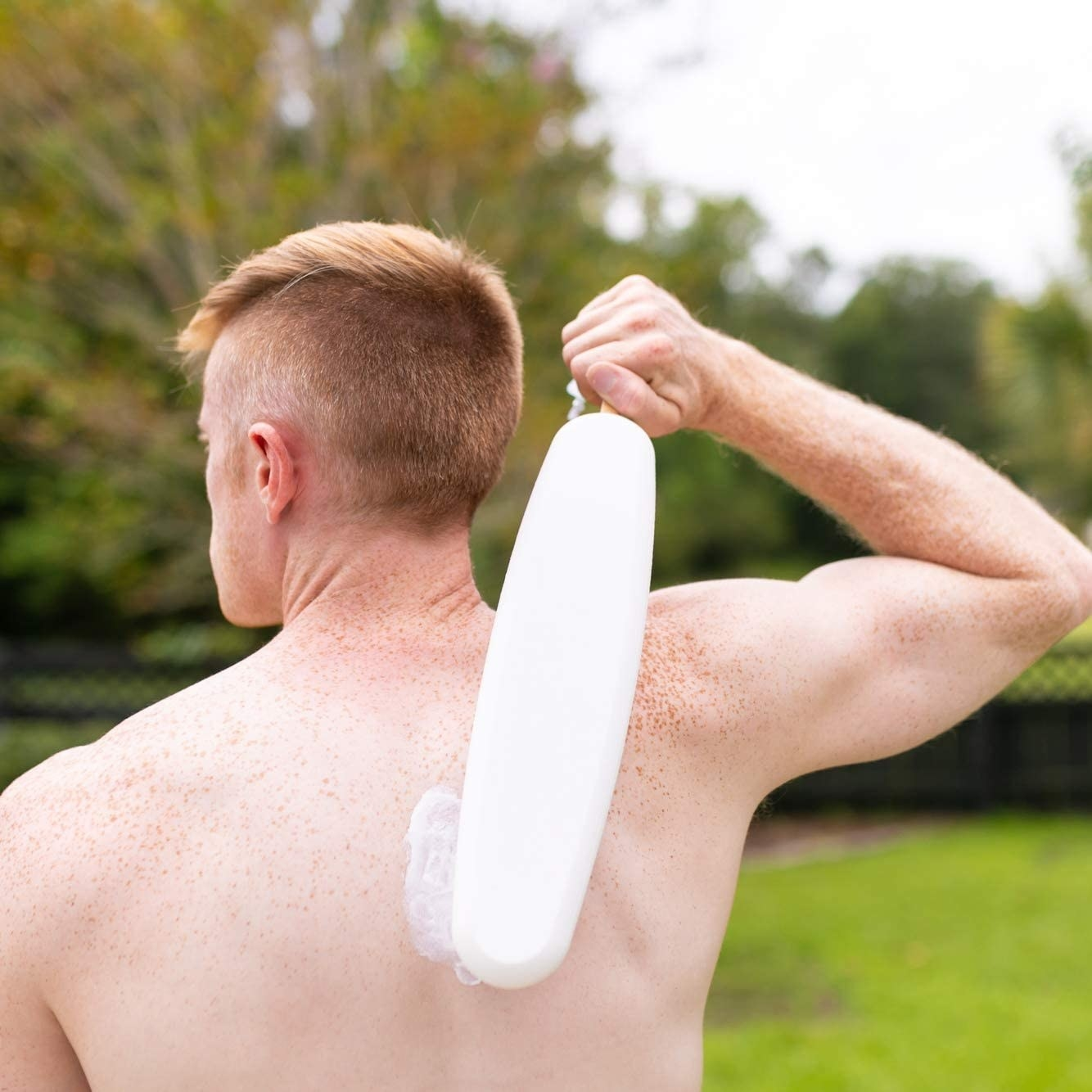 A person uses an applicator to spread a cream on their back