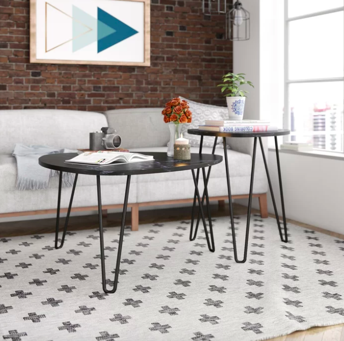 Black marble nesting tables placed next to each other on a criss-cross carpet