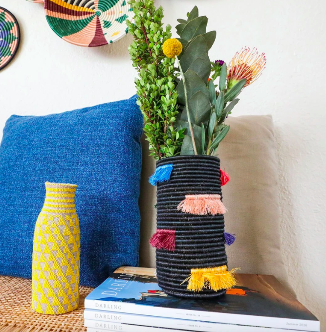 Black fringed vase with pink, magenta, blue, red, and purple tassels on the side
