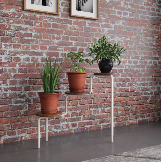 Wood and white three-tier plant stand with copper and black plant pots