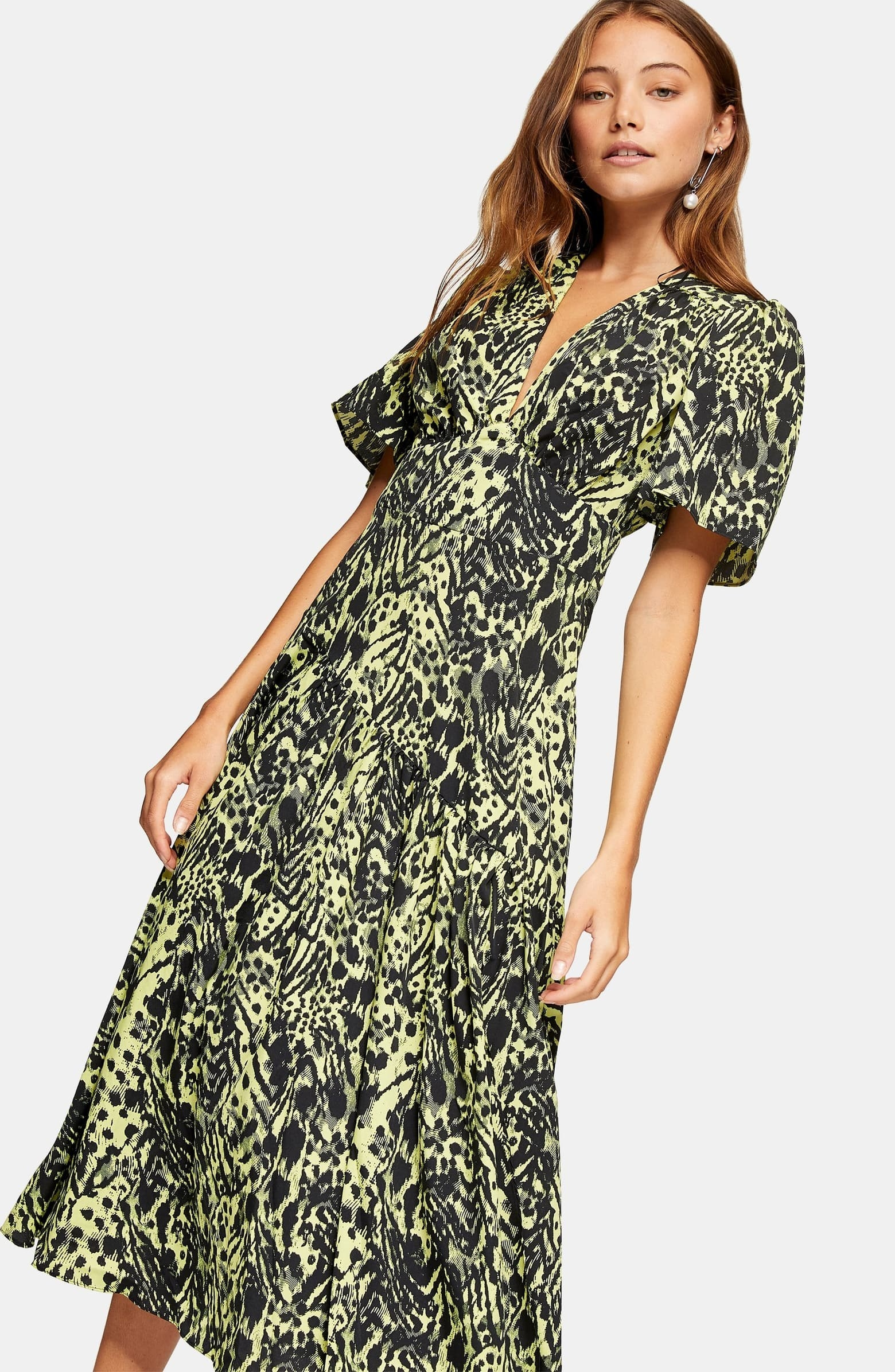 A model wears the bell-sleeved, short-sleeved dress with a v neck that comes in a little at the waist then flows out and down to their shins