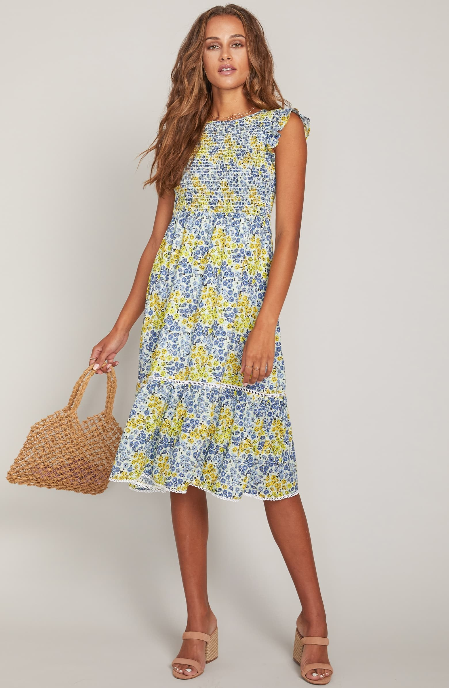 A model wears the floral dress with the smocked top that ends at the waist, where the dress flares slightly and hangs loosely down to the knees