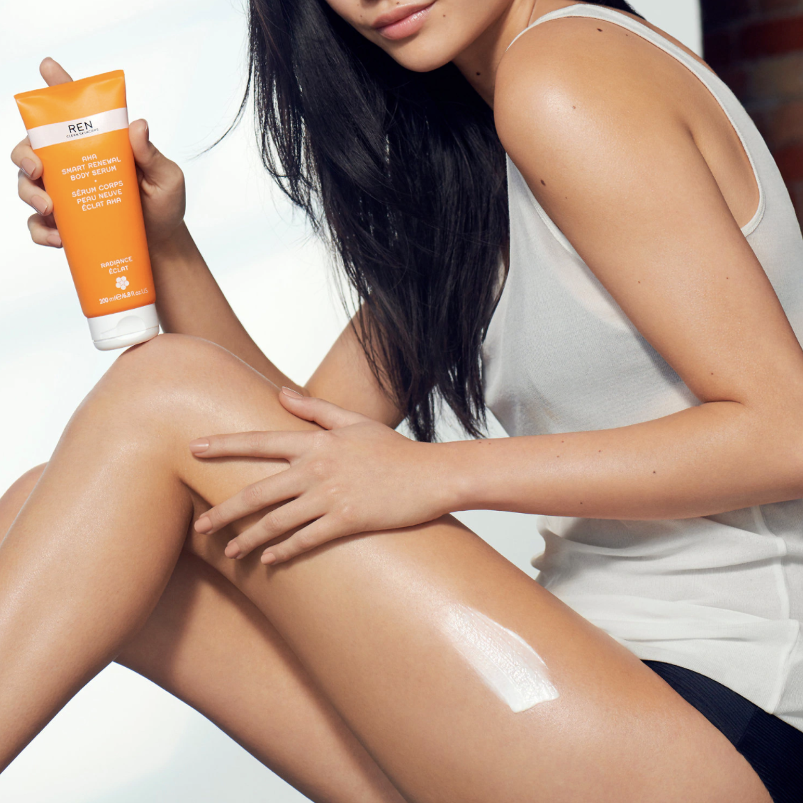 model with the bottle and a smudge of the product on her thigh