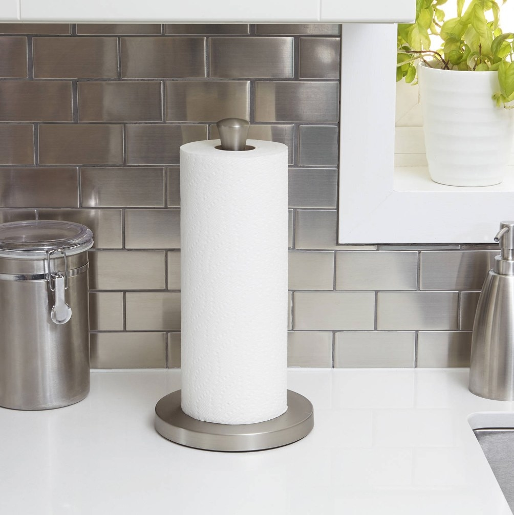 The silver paper towel holder on a white kitchen countertop