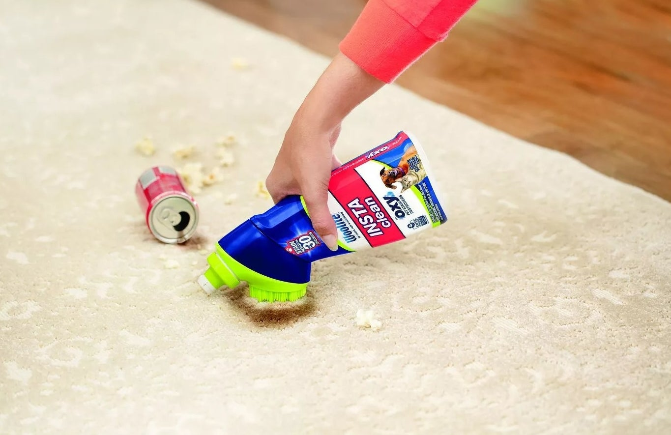 A model using Woolite's Insta-Clean stain remover to scrub a soda spill off of a rug