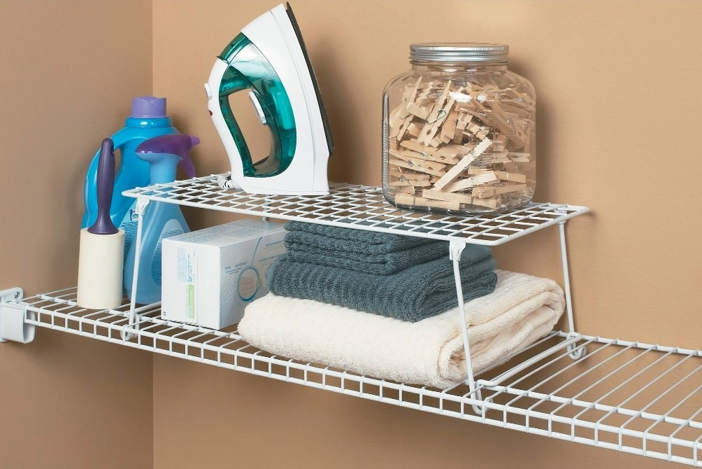 The white stacking shelf being used to hold towels, laundry detergent, and an iron