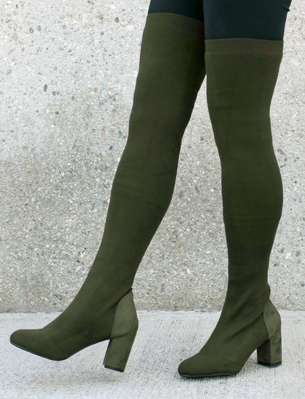 Model wearing green high-heeled, thigh-high boots