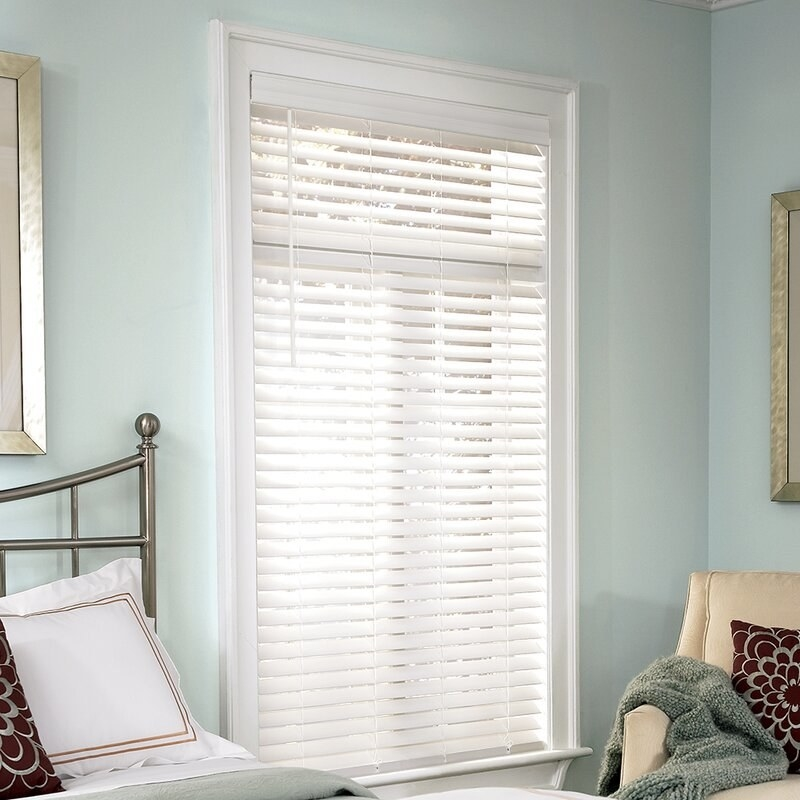 white venetian blinds hung in front of a window in a bedroom