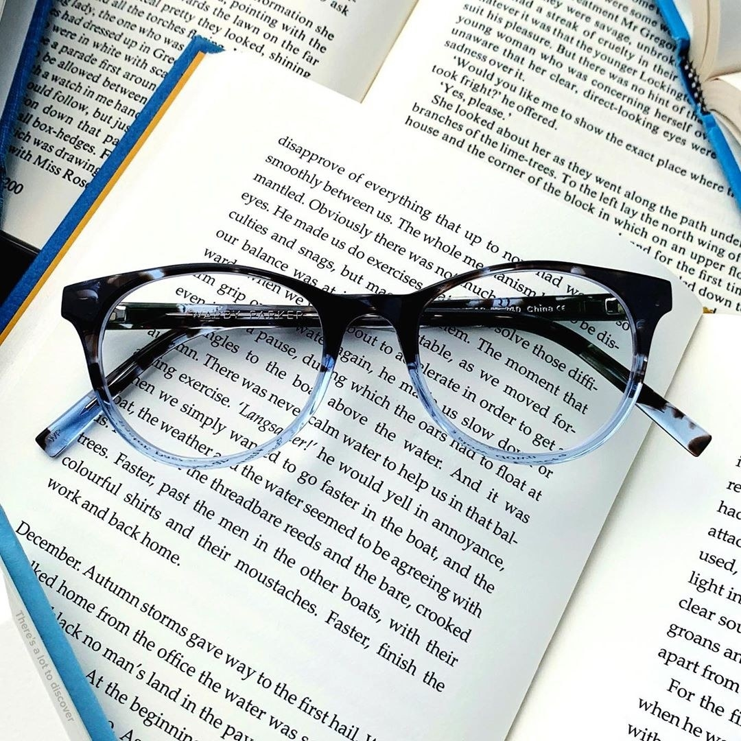 The glasses on top of several open books