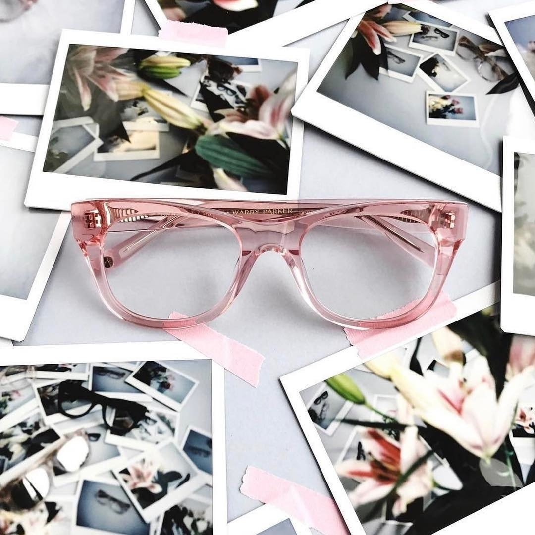 The glasses on a scrapbook filled with instant photos
