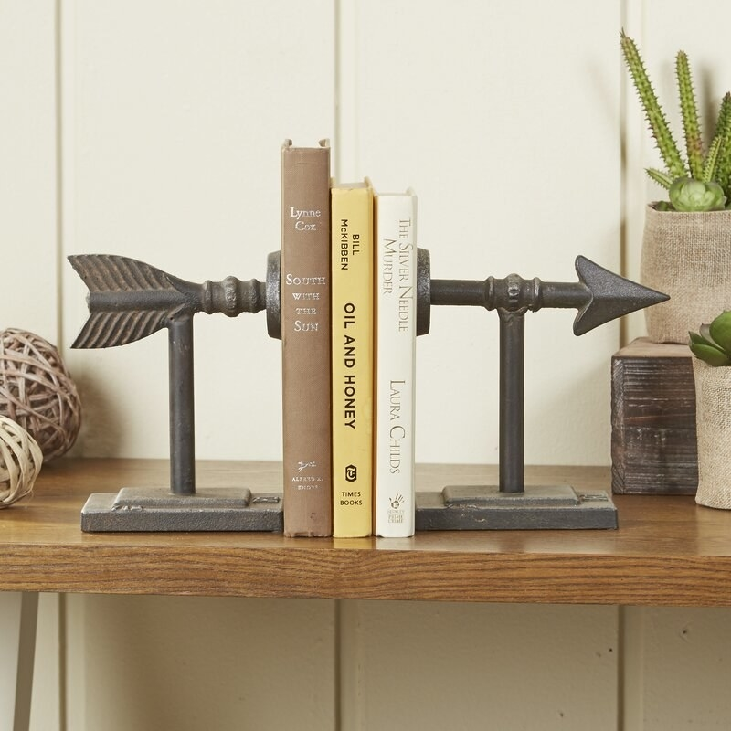 iron-appearing arrow bookends holding three books on a shelf