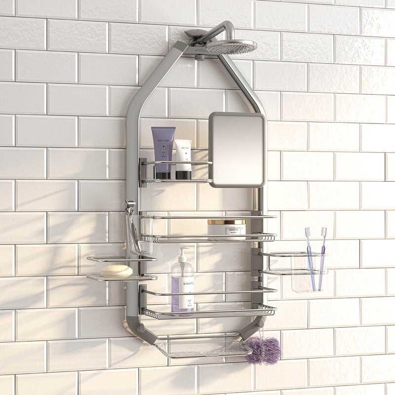A stainless steel shower caddy hung on a shower tap in a bathroom. the caddy holds soap, bottles, a loofah, and two toothbrushes