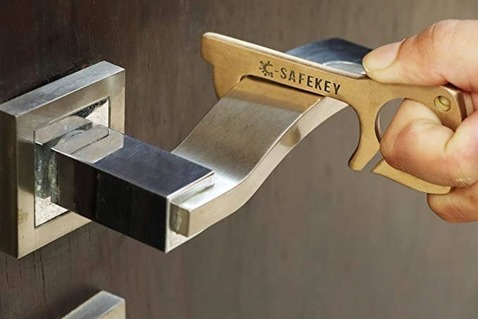 Door handle being pulled with the brass key opener.