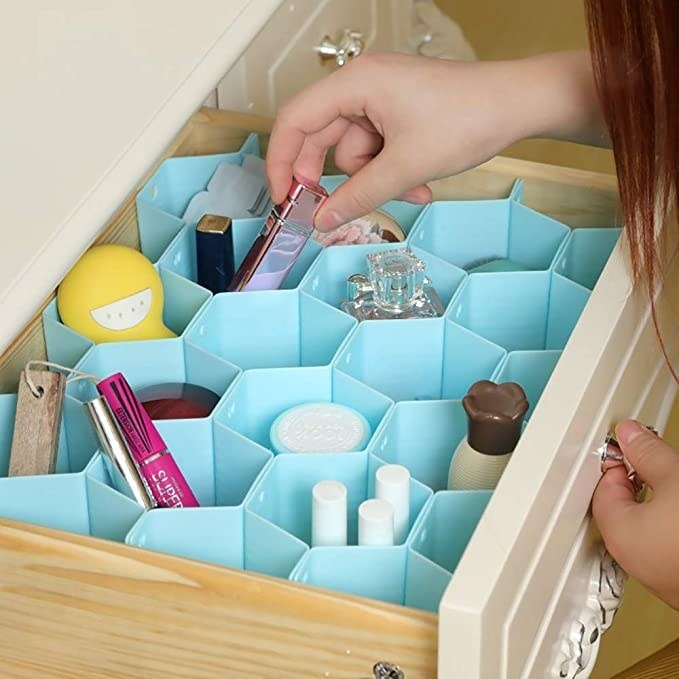 Woman organising make-up in a drawer with the help of the honeycomb dividers.