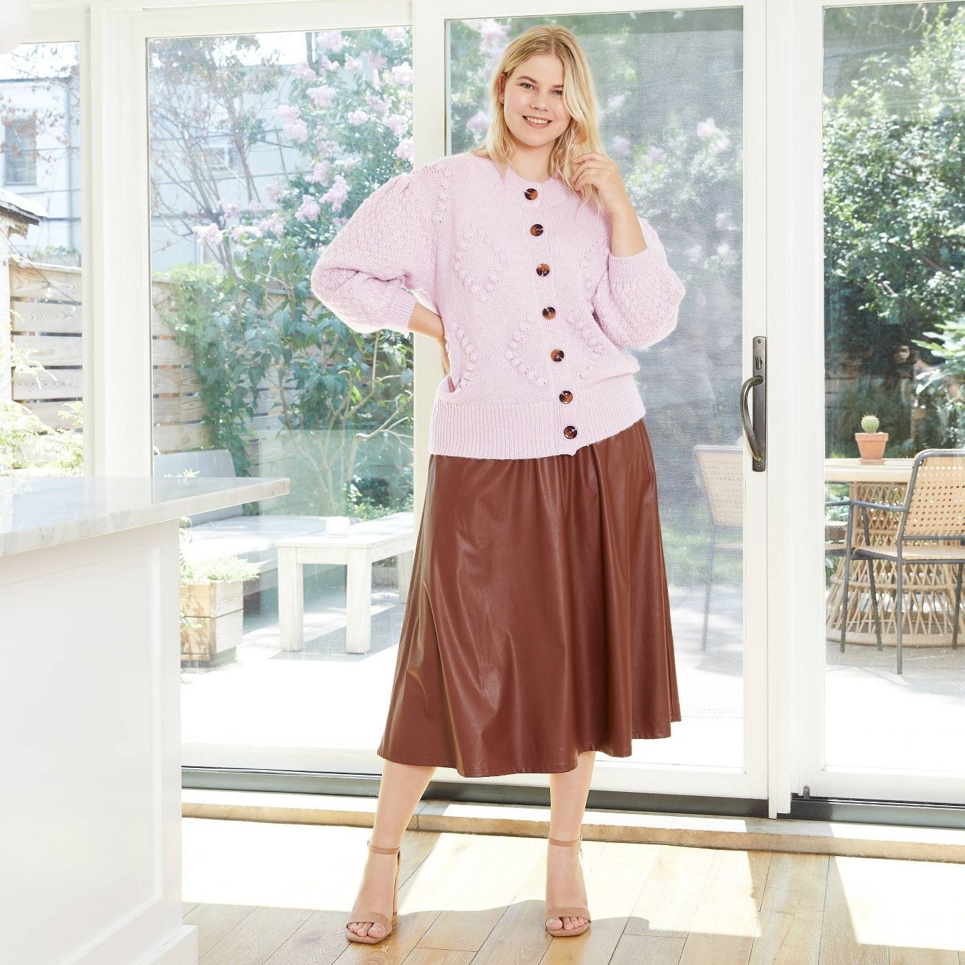 Model in light purple cardigan with brown buttons
