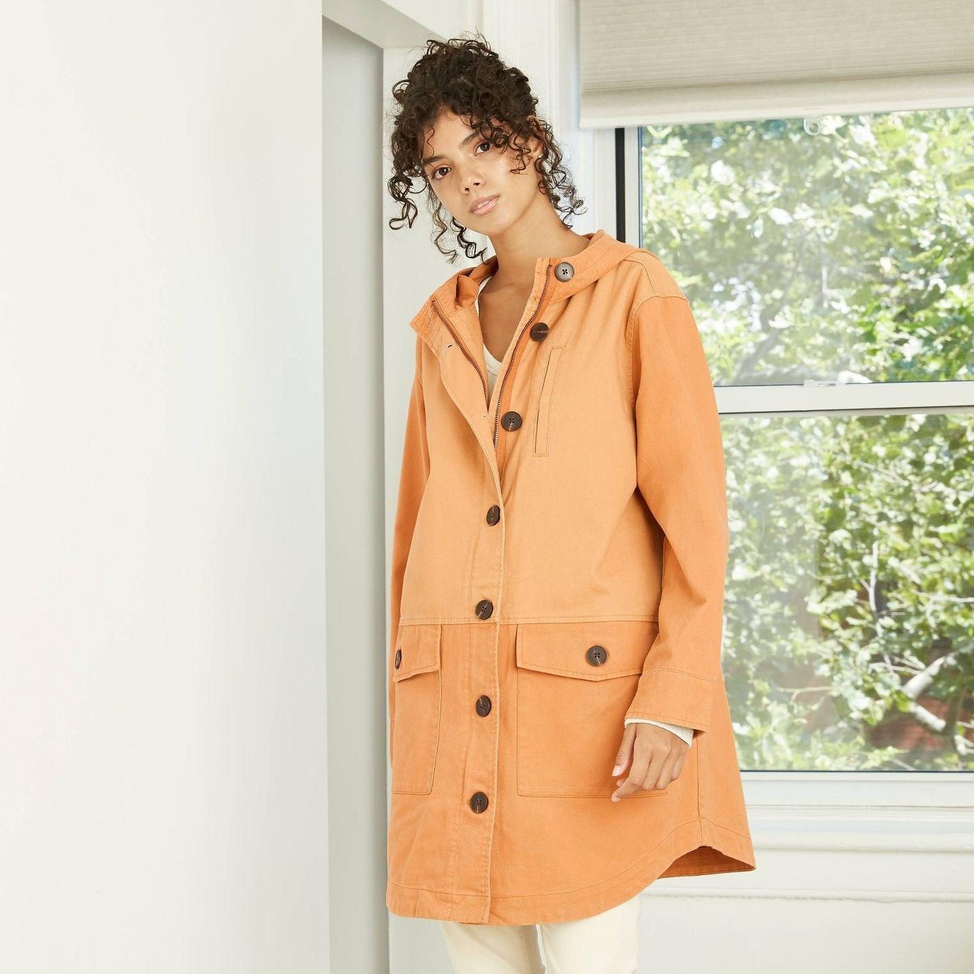 Model in orange color block jacket